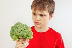 Menino cortado pequeno em um olhar vermelho da camisa em brócolis no fundo branco fotos de stock