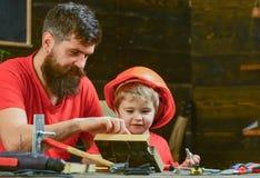 Menino, criança ocupada no capacete protetor aprendendo a martelar cravos com paizinho Conceito masculino dos deveres Pai, pai foto de stock
