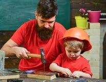 Menino, criança ocupada no capacete protetor aprendendo a martelar cravos com paizinho Pai, pai com barba que ensina pouco imagem de stock royalty free