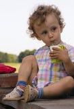Menino curly pequeno com suco nas mãos Imagem de Stock Royalty Free