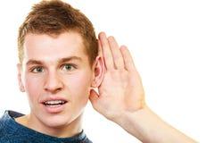 Menino da bisbolhetice com mão atrás de espiar da orelha Fotografia de Stock Royalty Free