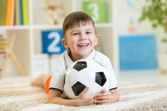 Menino da criança com a bola do pé interna Fotografia de Stock Royalty Free