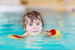 Menino da criança com swimmies que aprende nadar em uma piscina interior imagens de stock