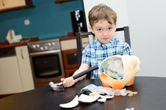 Menino da criança de 4 anos e despedaçado seu piggybank Imagens de Stock