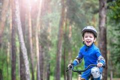 Menino da criança de 3 anos e seu pai na floresta do outono com uma bicicleta Filho de ensino do paizinho Homem feliz sobre o suc Imagens de Stock Royalty Free