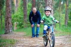 Menino da criança de 3 anos e seu pai na floresta do outono com uma bicicleta Filho de ensino do paizinho Homem feliz sobre o suc Fotografia de Stock Royalty Free