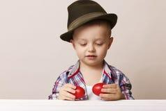 Menino da criança de 4 anos em um chapéu e em uma camisa que guardam ovos da páscoa vermelhos das mãos, Imagem de Stock Royalty Free