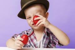 Menino da criança de 4 anos em um chapéu e em uma camisa que guardam ovos da páscoa vermelhos das mãos, Fotografia de Stock Royalty Free