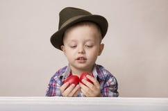 Menino da criança de 4 anos em um chapéu e em uma camisa que guardam ovos da páscoa vermelhos das mãos, Fotos de Stock Royalty Free