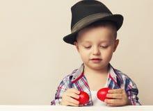 Menino da criança de 4 anos em um chapéu e em uma camisa que guardam ovos da páscoa vermelhos das mãos, Imagens de Stock