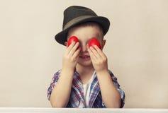 Menino da criança de 4 anos em um chapéu e em uma camisa que guardam ovos da páscoa vermelhos das mãos, Fotografia de Stock