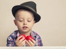 Menino da criança de 4 anos em um chapéu e em uma camisa que guardam ovos da páscoa vermelhos das mãos, Fotos de Stock