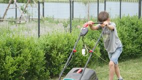 Menino da criança de dez anos que sega o gramado com um cortador de grama grande video estoque