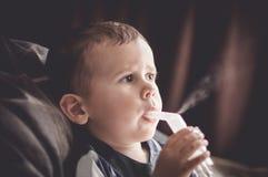 Menino da criança de dois anos que faz a inalação com nebulizer em casa fotos de stock