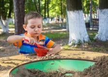 Menino da criança de quatro anos no campo de jogos no parque da cidade Imagens de Stock Royalty Free
