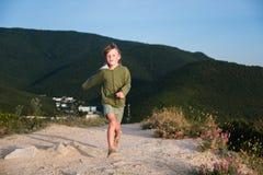 Menino da criança de seis anos que corre em uma estrada da montanha no por do sol com opinião da cidade Noite fresca do verão Fro fotos de stock