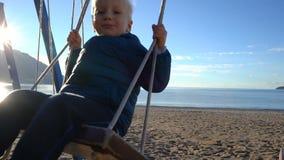 Menino da criança de três anos que balança em um balanço na manhã ensolarada na praia filme