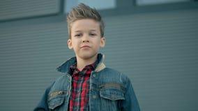 Menino da criança da forma do retrato que olha à câmera O menino modelo à moda bonito está levantando e está sorrindo video estoque