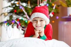 Menino da criança no chapéu de Santa com árvore de Natal e nas luzes no fundo Fotos de Stock
