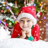 Menino da criança no chapéu de Santa com árvore de Natal e nas luzes no fundo Fotos de Stock Royalty Free