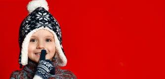 Menino da criança no chapéu feito malha e camiseta e mitenes que fazem para silenciar o gesto sobre o fundo vermelho colorido foto de stock