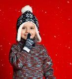 Menino da criança no chapéu feito malha e camiseta e mitenes que fazem para silenciar o gesto sobre o fundo vermelho colorido fotos de stock