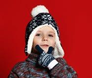 Menino da criança no chapéu feito malha e camiseta e mitenes que têm o divertimento sobre o fundo vermelho colorido imagem de stock royalty free