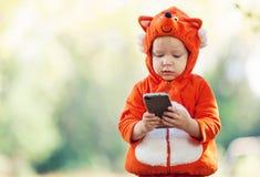 Menino da criança no traje da raposa que guarda o smartphone Fotografia de Stock Royalty Free