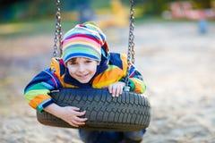 Menino da criança que balança no campo de jogos fora Imagens de Stock Royalty Free