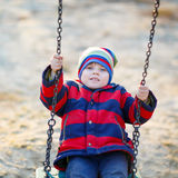 Menino da criança que balança no campo de jogos fora Imagem de Stock