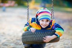 Menino da criança que balança no campo de jogos fora Foto de Stock Royalty Free