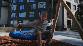 Menino da criança que balança no movimento lento do campo de jogos urbano video estoque