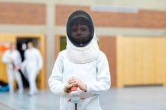 Menino da criança que cerca em uma competição da cerca Criança no uniforme branco do esgrimista com máscara e sabre Treinamento a fotografia de stock