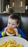 Menino da criança que come o Hamburger e as fritadas Fotos de Stock Royalty Free