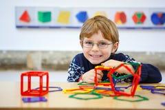 Menino da criança que constrói figuras geométricas com blocos plásticos Imagem de Stock