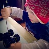 Menino da criança que fixa seu caminhão com uma faca de tabela Imagem de Stock Royalty Free