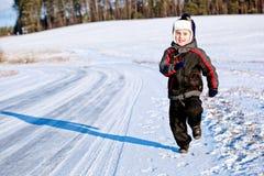 Menino da criança que funciona ao longo da estrada no inverno Foto de Stock