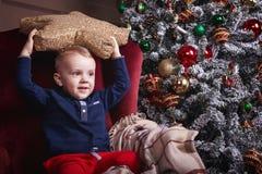 Menino da criança que guarda um descanso da forma da estrela perto da decoração do Natal fotos de stock royalty free