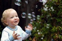 Menino da criança que joga com bolhas fotos de stock