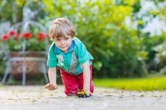 Menino da criança que joga com brinquedo do carro, fora Foto de Stock
