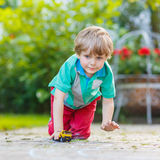 Menino da criança que joga com brinquedo do carro, fora Fotografia de Stock