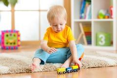 Menino da criança que joga com brinquedos dentro em casa ou jardim de infância Fotos de Stock