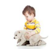 Menino da criança que joga com cão de cachorrinho imagem de stock