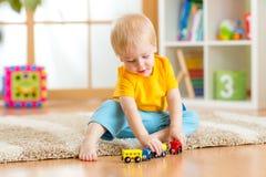 Menino da criança que joga com os brinquedos internos Imagens de Stock