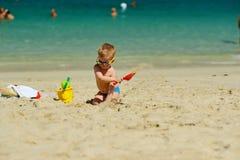 Menino da criança que joga com pá e areia na praia Fotografia de Stock