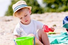 Menino da criança que joga com peneira da areia em uma praia imagem de stock