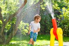Menino da criança que joga com uma mangueira e uma água de jardim Fotografia de Stock