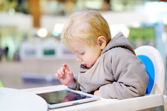 Menino da criança que joga com uma tabuleta digital imagens de stock royalty free