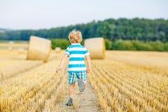 Menino da criança que joga no campo do feno, fora Imagem de Stock Royalty Free