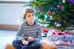 Menino da criança que joga o console do jogo de vídeo no Natal Fotos de Stock